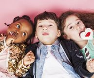 Lifestyle people concept: diverse nation children playing together, caucasian boy with african little girl holding candy. Happy smiling close up Stock Images
