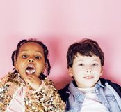 Lifestyle people concept: diverse nation children playing together, caucasian boy with african little girl holding candy Royalty Free Stock Photos
