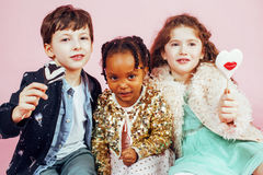 Lifestyle people concept: diverse nation children playing together, caucasian boy with african little girl holding candy Stock Photos