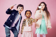 Lifestyle people concept: diverse nation children playing together, caucasian boy with african little girl holding candy Stock Image