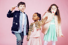 Lifestyle people concept: diverse nation children playing together, caucasian boy with african little girl holding candy Stock Images