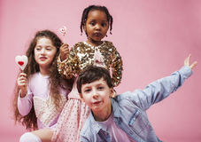 Lifestyle people concept: diverse nation children playing together, caucasian boy with african little girl holding candy Royalty Free Stock Images