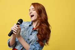 Lifestyle and People Concept: Expressive beauty ginger hair model girl in casual jean cloth singer with a microphone. Lifestyle and People Concept: Expressive Stock Photos