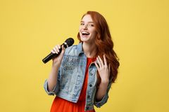 Lifestyle and People Concept: Expressive beauty ginger hair model girl in casual jean cloth singer with a microphone. Lifestyle and People Concept: Expressive Stock Photo