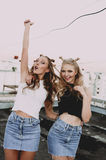 Lifestyle and people concept: Fashion portrait of two stylish girls best friends wearing jeans skirts, outdoors on the roof. Happy Royalty Free Stock Photography