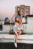Lifestyle and people concept: Fashion portrait of two stylish girls best friends wearing jeans skirts, outdoors on the roof. Happy Stock Images