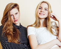 Lifestyle and people concept: Fashion portrait of two stylish sexy girls best friends, over white background. Happy time. For fun. One with hard feelings Royalty Free Stock Image