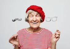 Lifestyle  and people concept: funny grandmother with fake mustache and glasses, laughs and prepares for  party stock image