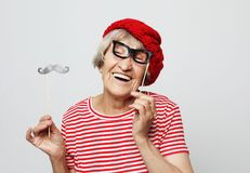Lifestyle  and people concept: funny grandmother with fake mustache and glasses, laughs and prepares for  party royalty free stock photos