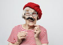 Lifestyle  and people concept: funny grandmother with fake mustache and glasses, laughs and prepares for  party stock images