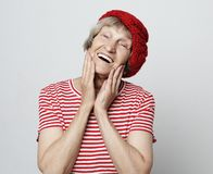 Lifestyle and people concept: grandmother dressed in a striped T-shirt and a red beret is smiling and holding her cheeks stock photo