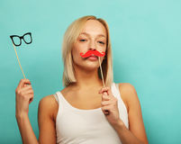 Lifestyle and people concept: Happy girl wearing fake mustaches and glasses over yellow background. Royalty Free Stock Photography
