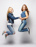 Lifestyle and people concept: Happy girls  jumping over white bq Royalty Free Stock Photography