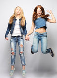Lifestyle and people concept: Happy girls  jumping over white bq Royalty Free Stock Photo