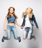 Lifestyle and people concept: Happy girls  jumping over white bq Royalty Free Stock Photos