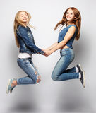 Lifestyle and people concept: Happy girls  jumping over white bq Royalty Free Stock Images