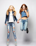 Lifestyle and people concept: Happy girls  jumping over white bq Stock Image