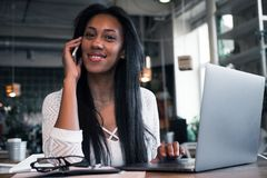 Lifestyle and people concept: happy young african woman in a coffee shop using mobile phone and laptop. Lifestyle and people concept: portrait of happy young Royalty Free Stock Image