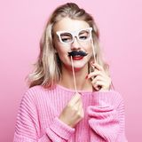 Lifestyle and people concept: playful young woman ready for party. Pink backgropund. Close up royalty free stock image