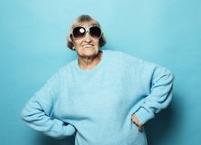 Lifestyle and people concept - portrait of a content senior lady wearing blue sweater smiling and looking at the camera stock photography