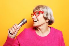 Lifestyle and people concept: Portrait of funny grandmother holds up the microphone stand and sings stock photos