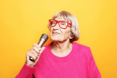 Lifestyle and people concept: Portrait of funny grandmother holds up the microphone stand and sings stock image