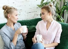 Lifestyle and people concept: Two beautiful women- mother and daughter sitting on the sofa at home. Lifestyle  and people concept: Two beautiful women- mother royalty free stock photos