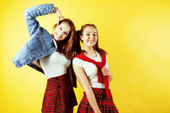 Lifestyle people concept: two pretty school girl having fun on yellow background, happy smiling students Royalty Free Stock Images