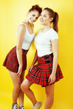 Lifestyle people concept: two pretty school girl having fun on yellow background, happy smiling students Royalty Free Stock Photography