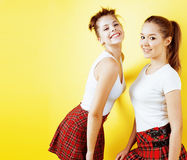Lifestyle people concept: two pretty school girl having fun on yellow background, happy smiling students Stock Image