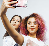 Lifestyle people concept: two pretty stylish modern hipster teen girl having fun together, diverse nation mixed races Royalty Free Stock Photo