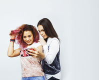 Lifestyle people concept: two pretty stylish modern hipster teen girl having fun together, diverse nation mixed races Royalty Free Stock Photos