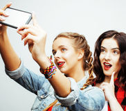 Lifestyle people concept: two pretty stylish modern hipster teen girl having fun together, happy smiling making selfie stock photos