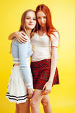 Lifestyle people concept: two pretty young school teenage girls having fun happy smiling on yellow background Stock Photos