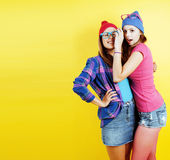 Lifestyle people concept: two pretty young school teenage girls having fun happy smiling on yellow background Royalty Free Stock Image
