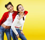Lifestyle people concept: two pretty young school teenage girls having fun happy smiling on yellow background Stock Photo