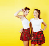 Lifestyle people concept: two pretty young school teenage girls having fun happy smiling on yellow background. Close up stock photography