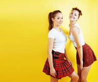 Lifestyle people concept: two pretty young school teenage girls. Having fun happy smiling on yellow background close up stock image