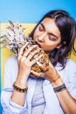 Lifestyle people concept. young pretty smiling indian girl with pineapple, asian summer fruits Royalty Free Stock Photo