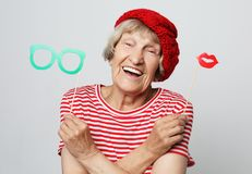 Lifestyle, people and party concept: funny grandmother wearing red clothes  ready for party stock photos