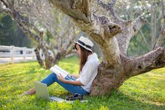 Lifestyle person Girl enjoy listening music and reading a book and play laptop on the grass field. Of the nature park in the morning. Lifestyle Concept royalty free stock photography