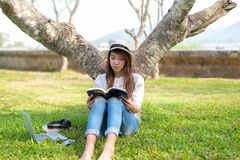 Lifestyle person Girl enjoy listening music and reading a book and play laptop on the grass field of the nature park in the mornin Stock Photo