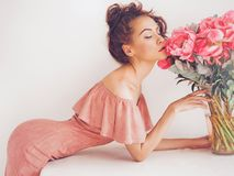 Beautiful woman with peonies. Lifestyle photo of beautiful young woman with pink peonies. Bouquet as gift. Emotions of happiness and joy. Valentines day. Mothers Royalty Free Stock Photo
