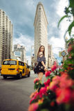 Lifestyle photo of elegant young adult woman traveling and walking on city street of New York. Royalty Free Stock Photo