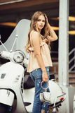Lifestyle photo of stylish beautiful woman walking on city street and turning back in front of moped. Stock Photography
