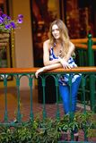 Lifestyle portrait. Young, caucasian female casually leaning on a terrace balcony Royalty Free Stock Image