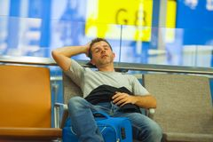 Lifestyle portrait in airport of young attractive and tired tourist man with suitcase sleeping at boarding gate waiting for cancel. Led or delayed flight stock photos