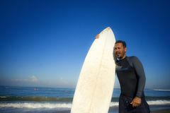 Lifestyle portrait of attractive and cool surfer man 3os to 40s in neoprene surfing swimsuit posing with surf board on the beach royalty free stock photos