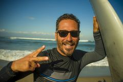 Lifestyle portrait of attractive and happy surfer man 3os to 40s in neoprene surfing swimsuit posing with surf board on the beach stock photo