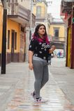 Lifestyle portrait of a beautiful young plus size woman. Smiling at camera in the city street stock photo